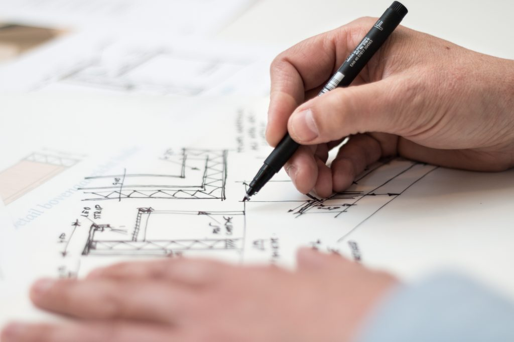 image of a person with black pen sketching designs on a piece of paper