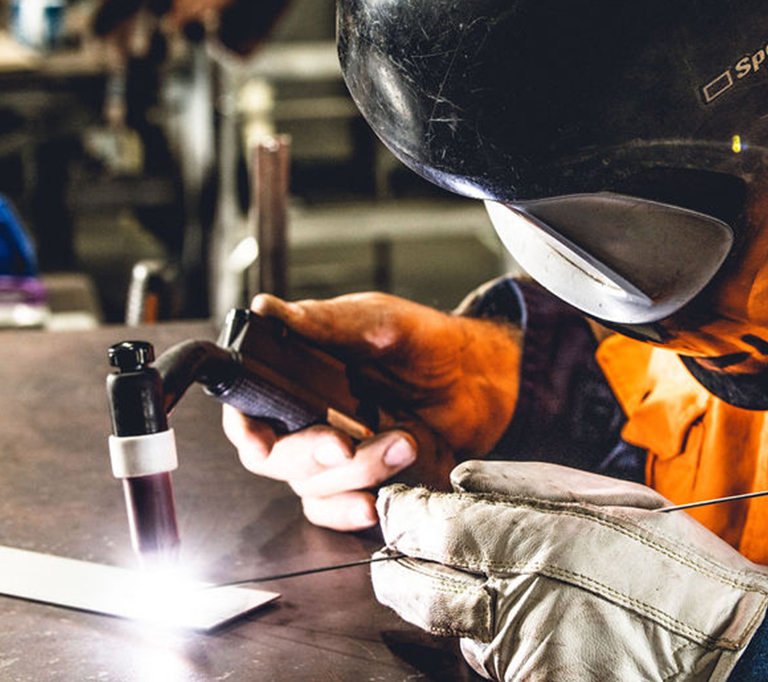 person welding with safety glasess and gloves